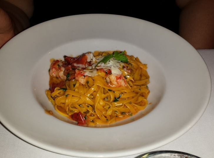 A photograph of a plate of linguine with red prawns, herbs and cheese.
