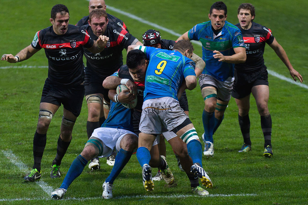 A photograph of Christopher Tolofua of Stade Toulousian charging the defense of the Beneton Rugby Treviso team. Image taken during the Heineken Cup on 13 January 2013 at the Stade Ernest-Wallon in the match between Stade Toulousain and Benetton Rugby Treviso.