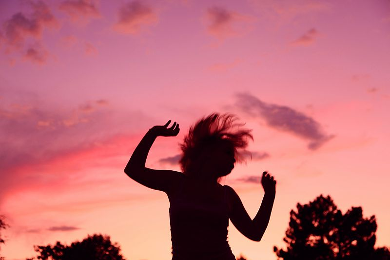 A photograph of a silhouetted woman dancing during a sunset.